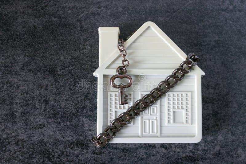 Mały bielu dom, łańcuch i dekoracyjny klucz na ciemnym backgrou, fotografia royalty free