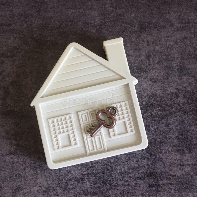 Mały bielu dom i dekoracyjny klucz na ciemnym tle przeciw zdjęcia stock