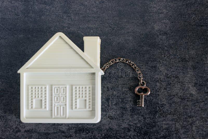 Mały bielu dom i dekoracyjny klucz na ciemnym tle przeciw obrazy stock