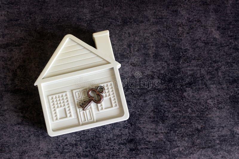 Mały bielu dom i dekoracyjny klucz na ciemnym tle przeciw obraz stock