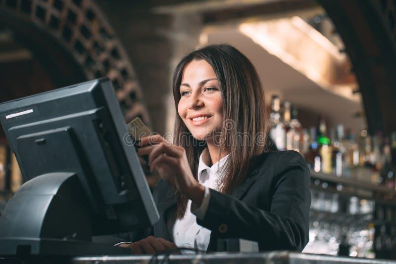Mały biznes, ludzie i usługowy pojęcie, - szczęśliwa kobieta, kelner lub kierownik w fartuchu przy kontuarem z cashbox fotografia stock