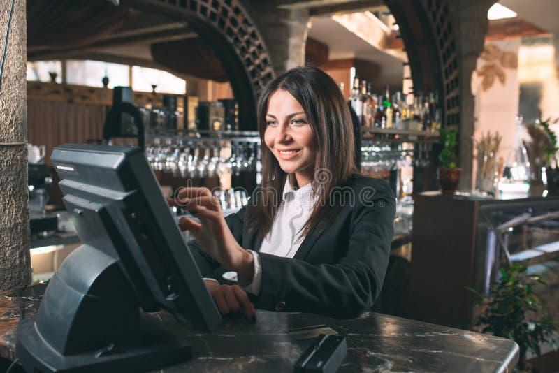 Mały biznes, ludzie i usługowy pojęcie, - szczęśliwa kobieta, kelner lub kierownik w fartuchu przy kontuarem z cashbox obrazy royalty free
