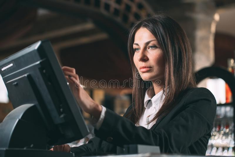 Mały biznes, ludzie i usługowy pojęcie, - szczęśliwa kobieta, kelner lub kierownik w fartuchu przy kontuarem z cashbox obrazy stock