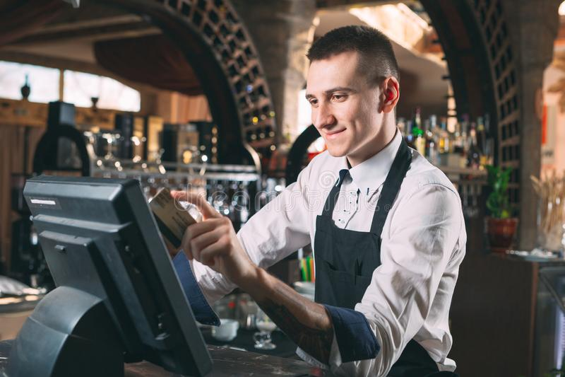 Mały biznes, ludzie i usługowy pojęcie, - szczęśliwy mężczyzna lub kelner w fartuchu przy kontuarem z cashbox pracuje przy barem  obrazy royalty free