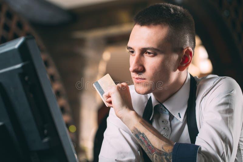 Mały biznes, ludzie i usługowy pojęcie, - szczęśliwy mężczyzna lub kelner w fartuchu przy kontuarem z cashbox pracuje przy barem  fotografia royalty free