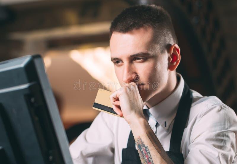 Mały biznes, ludzie i usługowy pojęcie, - szczęśliwy mężczyzna lub kelner w fartuchu przy kontuarem z cashbox pracuje przy barem  obraz royalty free
