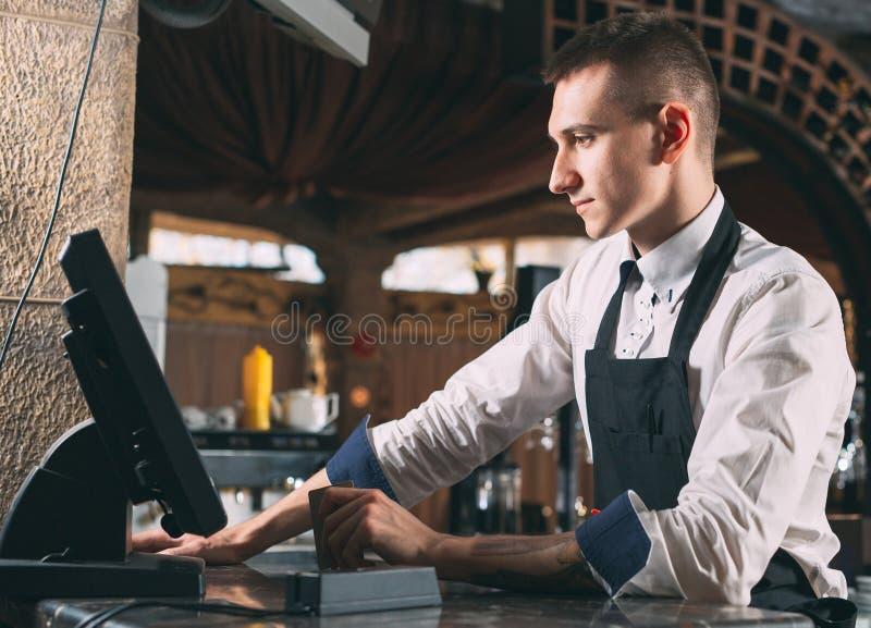 Mały biznes, ludzie i usługowy pojęcie, - szczęśliwy mężczyzna lub kelner w fartuchu przy kontuarem z cashbox pracuje przy barem  obraz stock