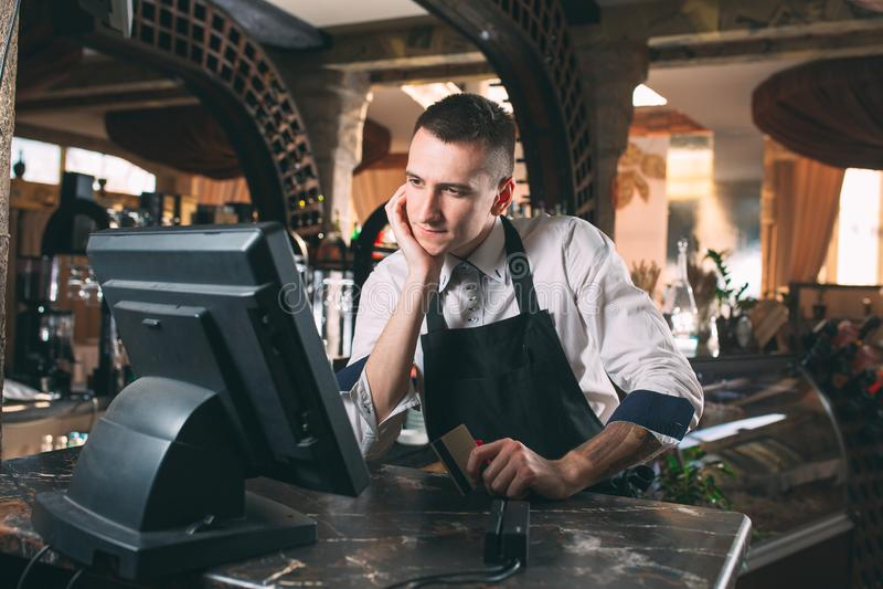 Mały biznes, ludzie i usługowy pojęcie, - szczęśliwy mężczyzna lub kelner w fartuchu przy kontuarem z cashbox pracuje przy barem  obrazy stock