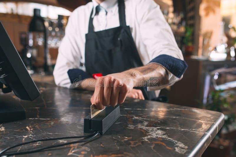 Mały biznes, ludzie i usługowy pojęcie, - szczęśliwy mężczyzna lub kelner w fartuchu przy kontuarem z cashbox pracuje przy barem  zdjęcie royalty free