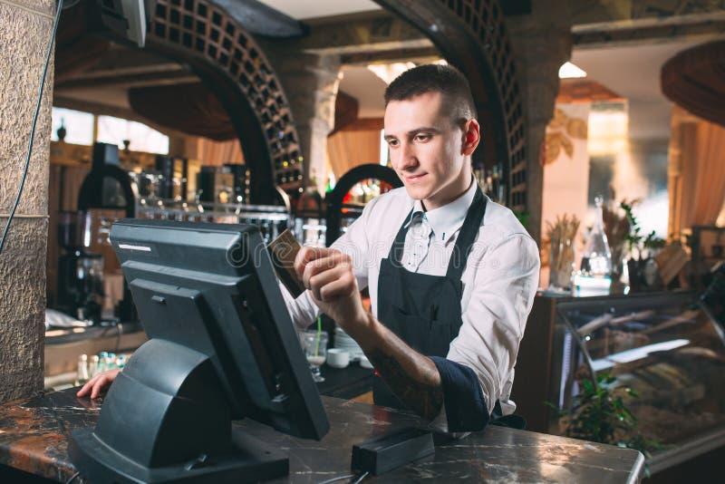Mały biznes, ludzie i usługowy pojęcie, - szczęśliwy mężczyzna lub kelner w fartuchu przy kontuarem z cashbox pracuje przy barem  fotografia stock