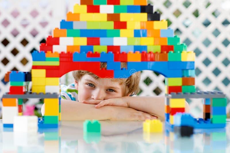 Mały blond dziecko bawić się z udziałami kolorowi plastikowi bloki Urocza preschool dzieciak chłopiec jest ubranym kolorową koszu obrazy stock