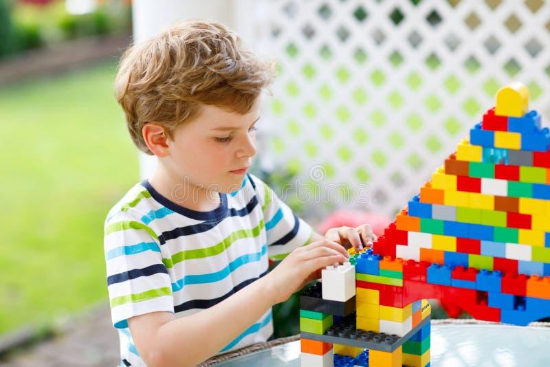 Mały blond dziecko bawić się z udziałami kolorowi plastikowi bloki Urocza preschool dzieciak chłopiec jest ubranym kolorową koszu zdjęcie stock