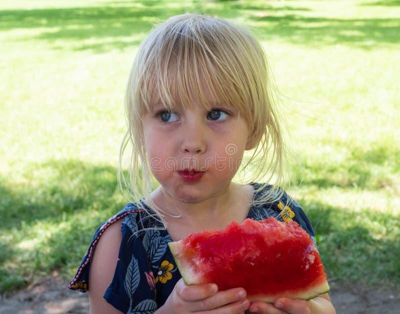 Mały blondynki dziewczyny łasowania arbuz obraz stock