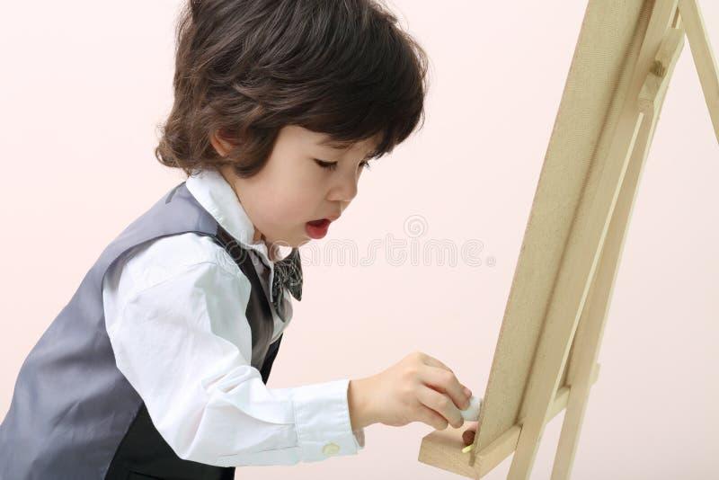 Mały brunet koncentrująca chłopiec rysuje kredą przy chalkboard obraz royalty free