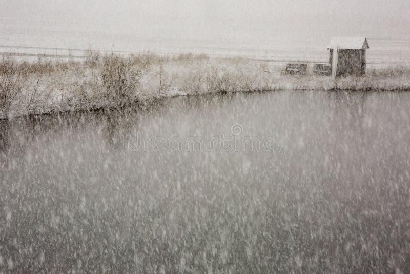 Mały budynek na stawie podczas śnieżycy fotografia stock