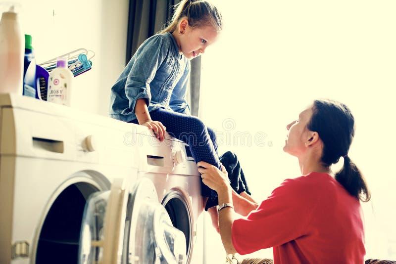 Mały córki obsiadanie na pralnianej maszynie zdjęcia royalty free