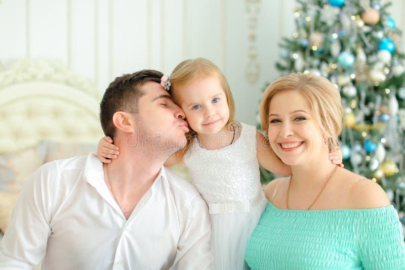 Mały córki obsiadanie z całowanie ojcem i blondynki macierzystą pobliską dekorującą choinką obraz stock
