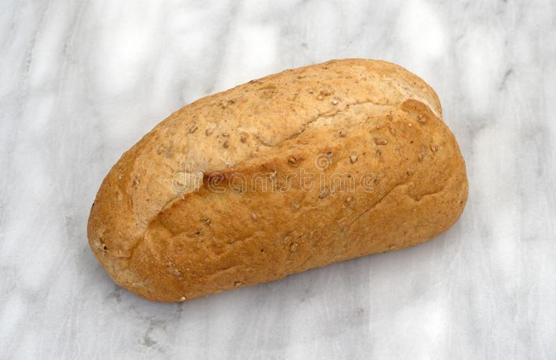 Mały całej banatki chleba bochenek na tnącej desce obraz stock