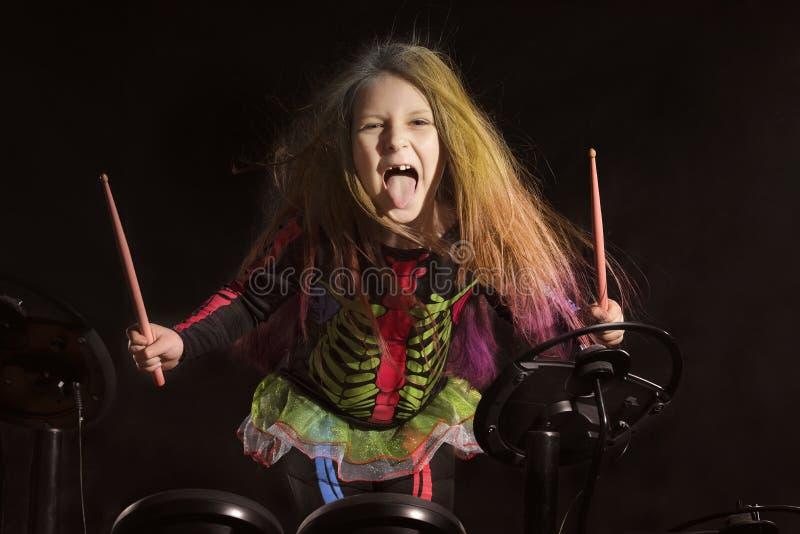 Mały caucasian dziewczyna dobosz z stubarwnym włosy bawić się elektronicznego bębenu zestaw fotografia royalty free