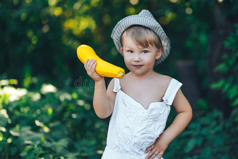 Mały chłopczyk trzymający żółte zupy cukinii w letnim ogrodzie, chłopak w białym, luźnym szacie i kapeluszu obrazy royalty free