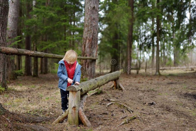 Mały chłopiec pił gałąź z małym nożem na długim, wyciętym kłód, chodząc w lesie wiosną fotografia stock