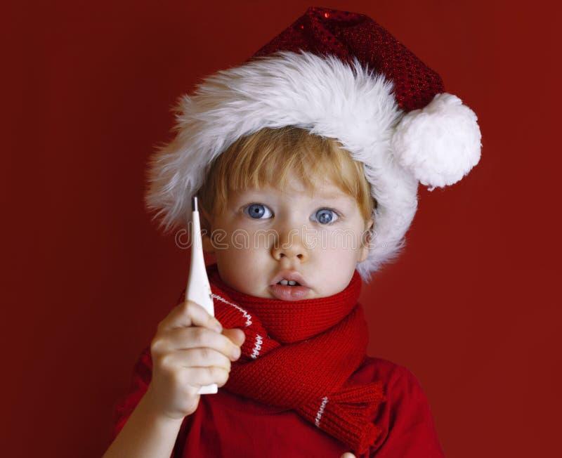Mały chłopiec w czerwonej kapeluszu santa trzyma termometr Dziecko jest chore przed Bożym Narodzeniem fotografia royalty free
