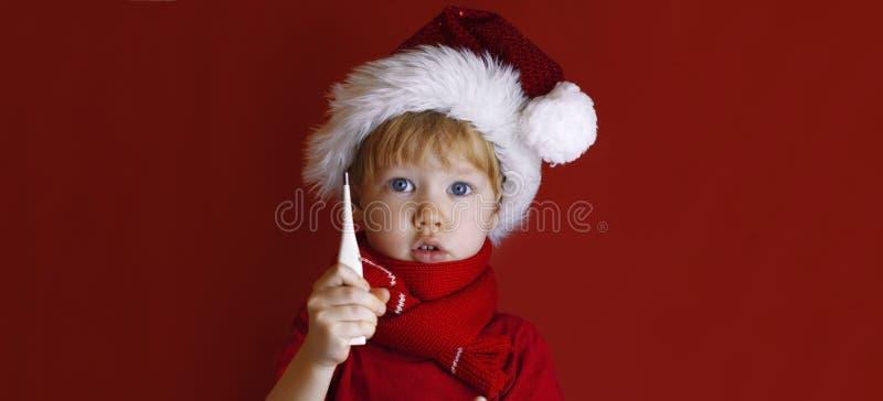 Mały chłopiec w czerwonej kapeluszu santa trzyma termometr Dziecko jest chore przed Bożym Narodzeniem obrazy stock