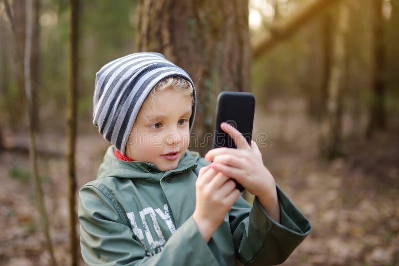 Mały chłopiec wykonujący zdjęcia lub wideorozmowę ze smartfonem podczas spaceru w lesie wiosną lub jesienią obraz stock