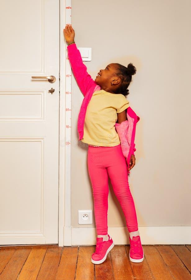 Mały czarny dziewczyny nabranie patrzeć wysoki na drzwi skali obraz royalty free