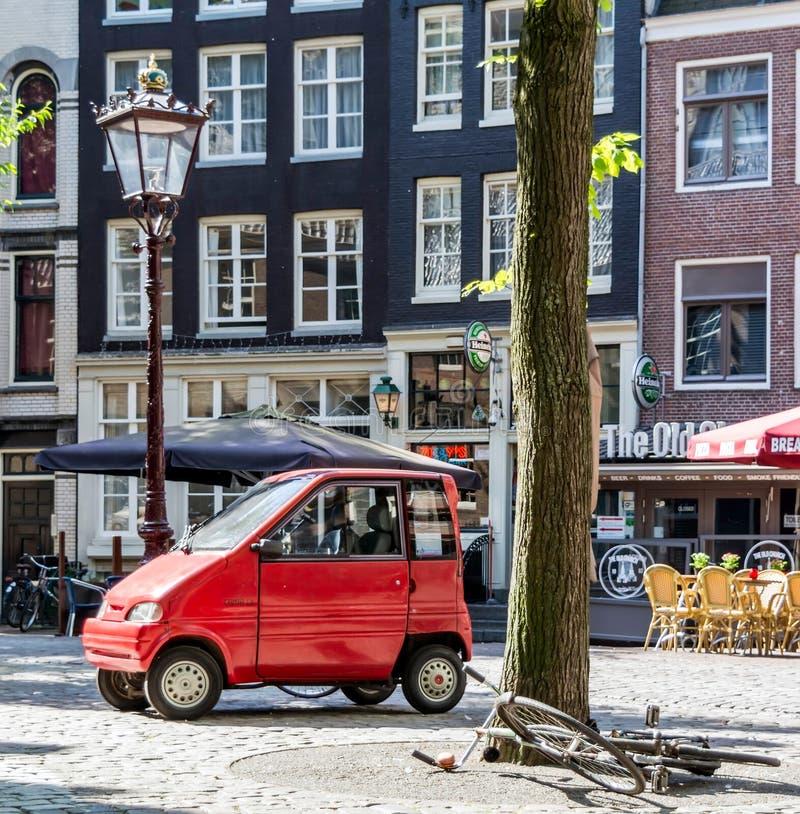 Mały czerwony samochód i łgarski bicykl pod drzewem na ulicie Amsterdam fotografia stock