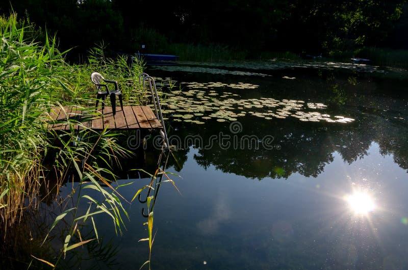 Mały dok przy jeziornym odbiciem na wodzie zdjęcie stock
