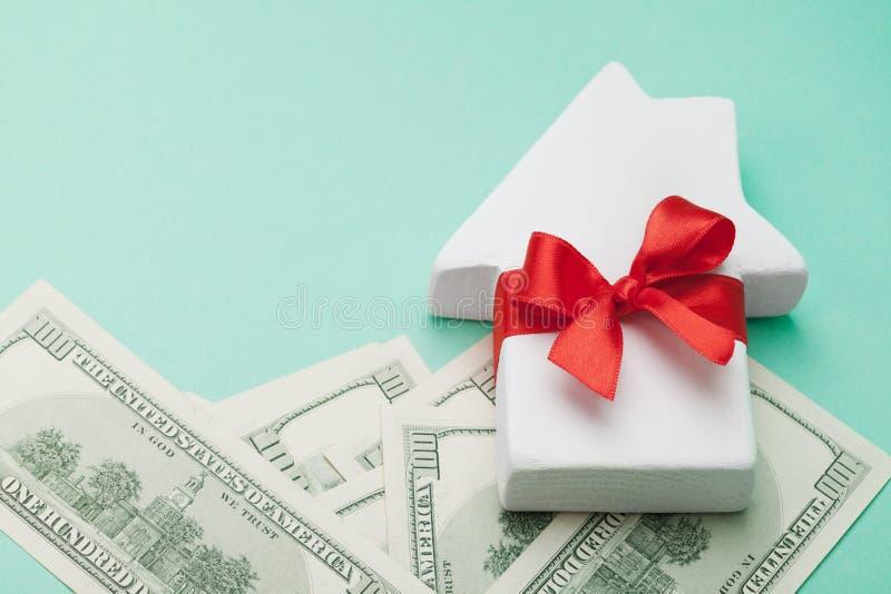 Mały dom dekorujący bielu łęku czerwony faborek i dolary pieniądze na zielonym tle Kupować dom, prezent lub sprzedaż nieruchomość zdjęcie stock