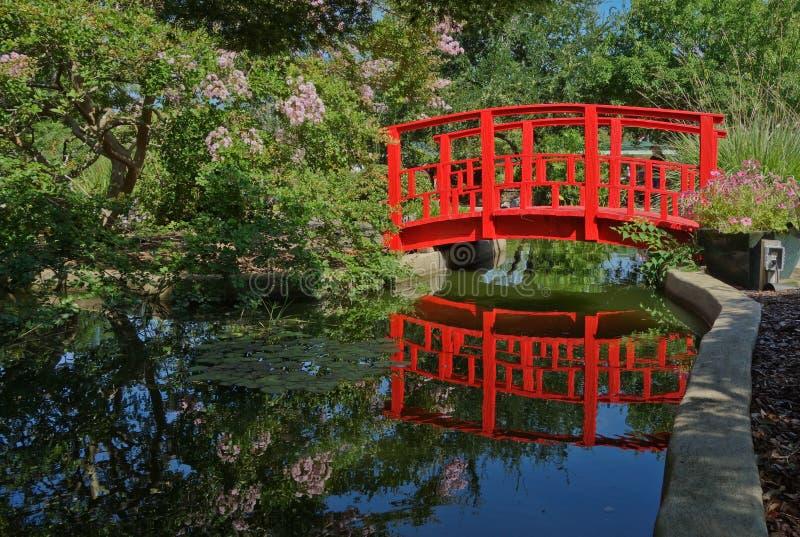 Mały drewniany most malował czerwonego i odbijać w stawie obrazy royalty free