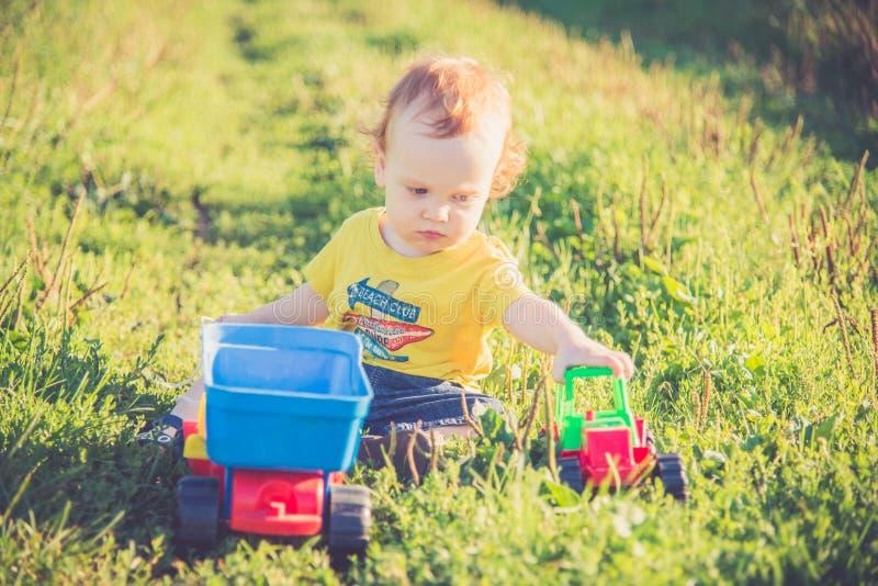 Mały dzieciak w naturze bawić się z zabawkarskimi samochodami obrazy royalty free