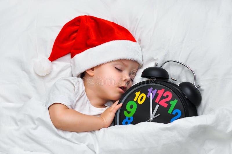 Mały dziecka dosypianie na białej pościeli w Santa kapeluszu i alarm pokazujemy pięć minut jedenaście fotografia stock