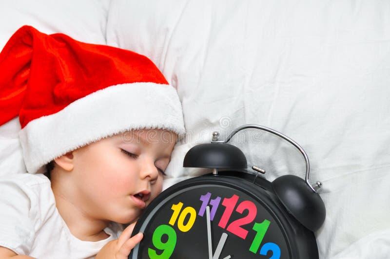 Mały dziecka dosypianie na białej pościeli w Santa kapeluszu i alarm pokazujemy pięć minut jedenaście obrazy stock