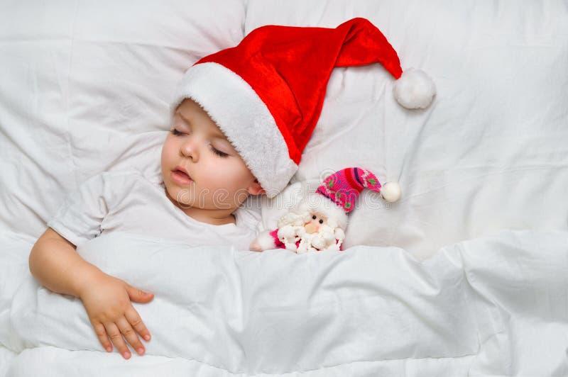 Mały dziecka dosypianie na białej pościeli w Santa kapeluszu z jego zabawkarskim Święty Mikołaj obrazy stock
