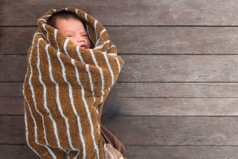 Mały dziecka lying on the beach z futerkową tkaniną na drewno stole obraz royalty free