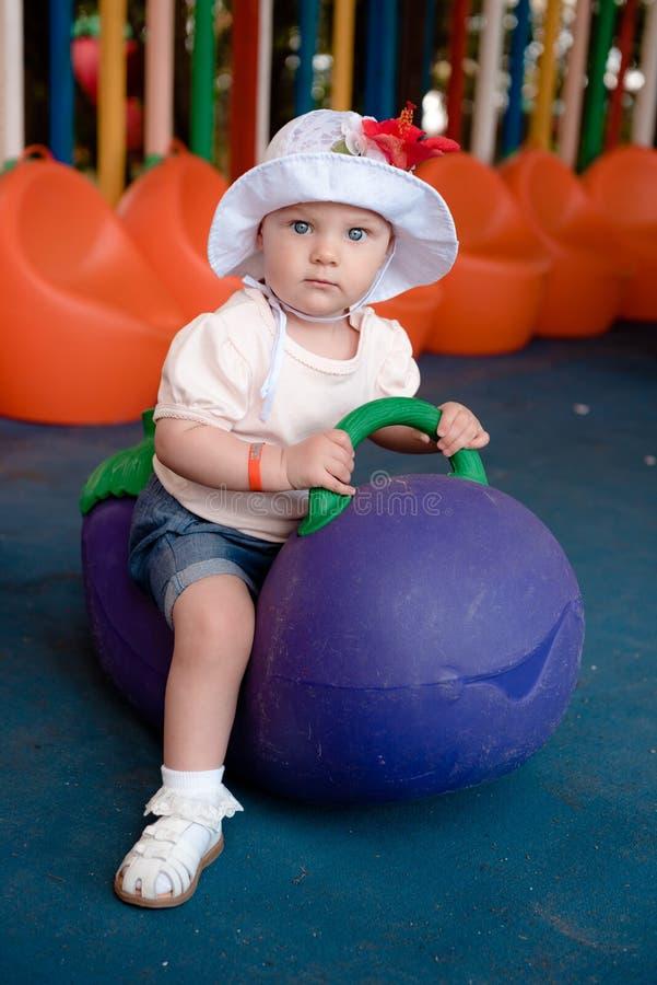 Mały dziecka obsiadanie na wielkiej oberżynie w boisku obrazy royalty free