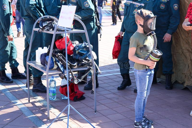 Mały dziecko jest ubranym ochronną maskę w masce gazowej i trzyma pudełko maski gazowe w Białoruś, Minsk, 08 08 2018 zdjęcie stock
