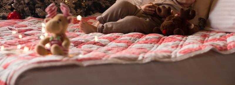 Mały dziecko kłama na łóżku z łosiem amerykańskim blisko nowego roku drzewa, trzyma telefon, pastylka boże narodzenie las moletow obraz royalty free