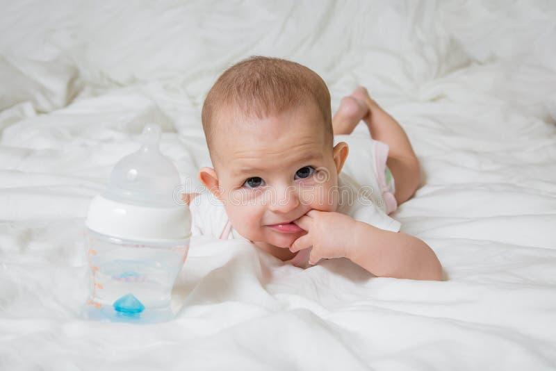 Mały dziecko kłama na białym łóżku na jego żołądku Dziewczyna stawia dwa palca w jej usta W pobliżu jest plastikowy butelka tam obraz royalty free