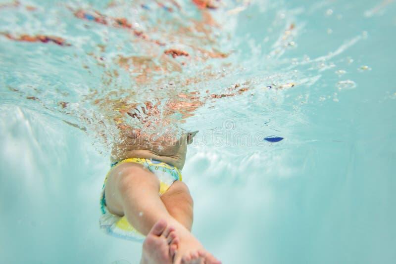 Mały dziecko pływa pod wodą dziecko angażuje w akwalungu pikowaniu fotografia royalty free