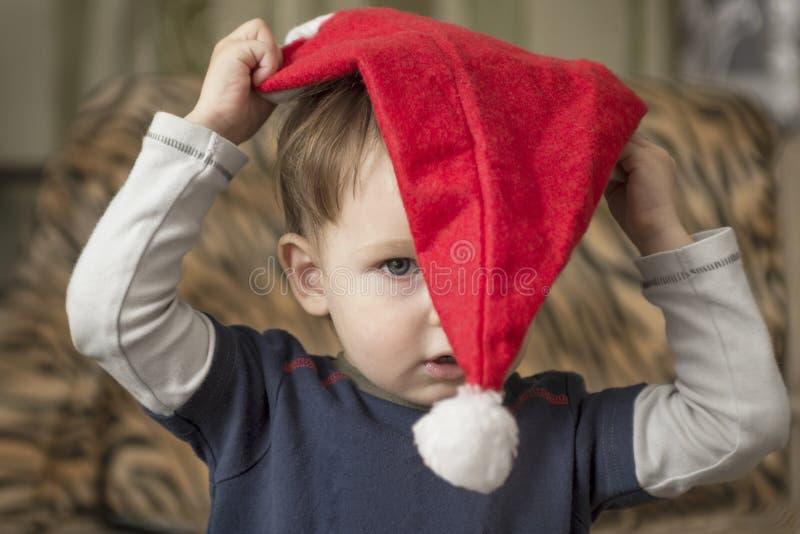Mały dziecko próbuje stawiać dalej Święty Mikołaj kapelusz obrazy royalty free