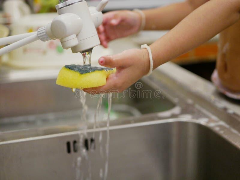Mały dziecko ręki mienia dishwashing gąbki chlapnąć w wodzie, gdy był płuczkowym kuchennym zlew sama zdjęcia royalty free