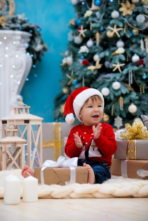 Mały dziecko Santa Claus w bożych narodzeniach kapeluszowych boże narodzenie nowy rok szczęśliwy wesoło Wakacje i prezenty dla dz zdjęcia stock