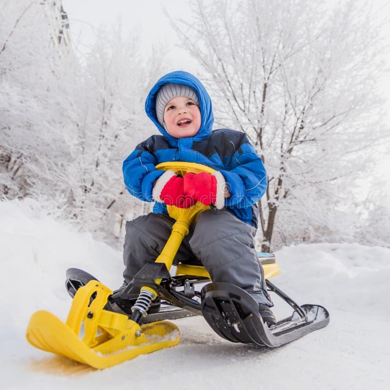 Mały dziecko siedzi na śnieżnej hulajnodze w zimie obrazy stock