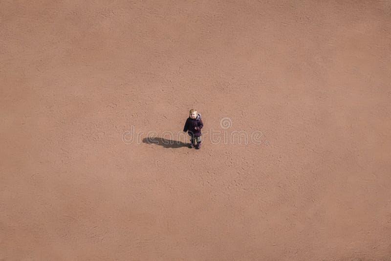 Mały dziecko stoi po środku piaskowatej pustyni, conce obraz royalty free