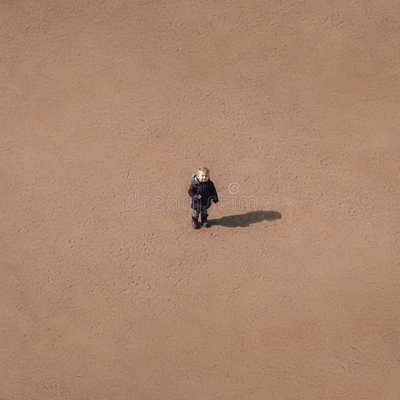 Mały dziecko stoi po środku piaskowatej pustyni, conce obrazy royalty free