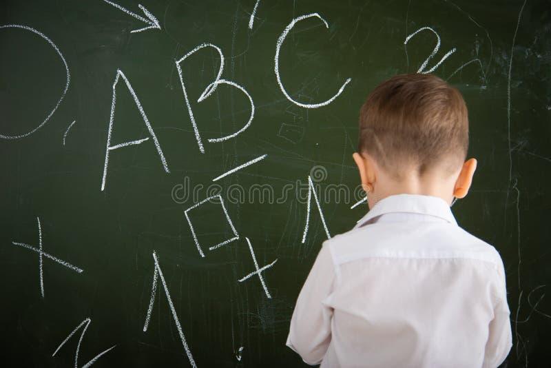 Mały dziecko stoi przy zarządem szkołym zdjęcie stock